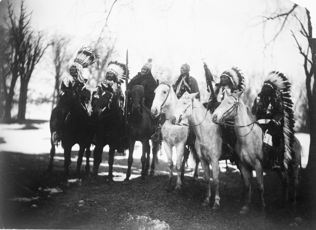 Six tribal leaders (l to r) Little Plume (Piegan), Buckskin Charley (Ute), Geronimo (Chiricahua Apache), Quanah Parker (Comanche), Hollow Horn Bear (Brulé Sioux), and American Horse (Oglala Sioux) on horseback in ceremonial attire. This image is available from the United States Library of Congress's Prints and Photographs division.